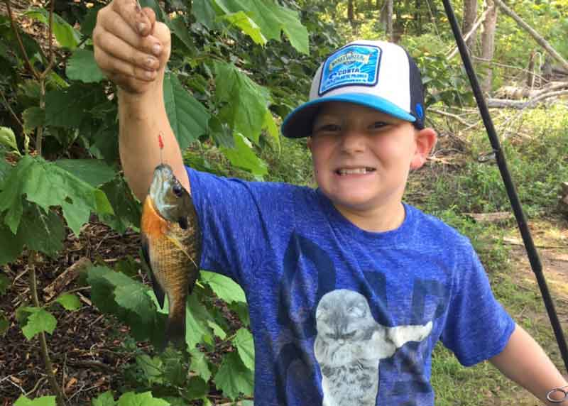 kid holds up a bluegill