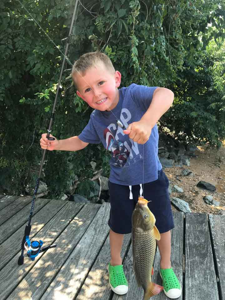 a boy catches his first carp