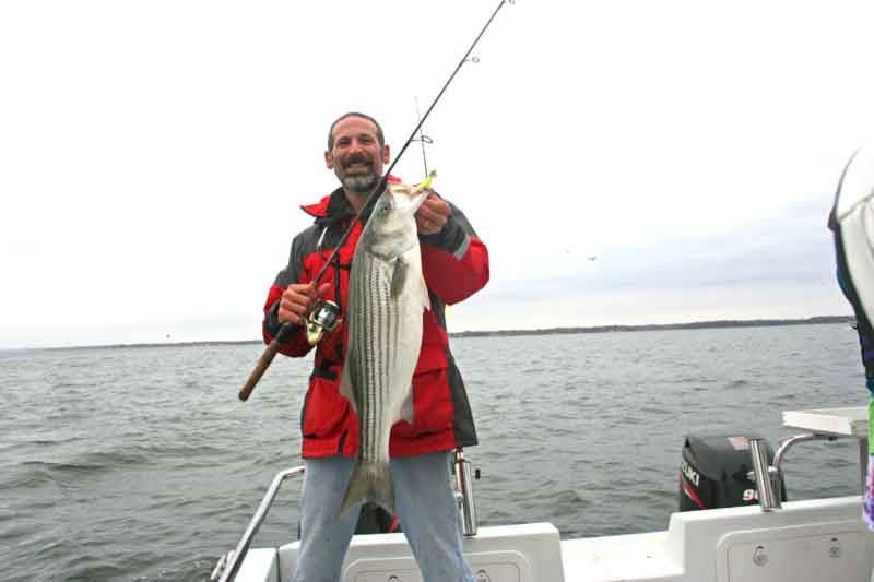 angler with a rockfish caught near an artificial reef