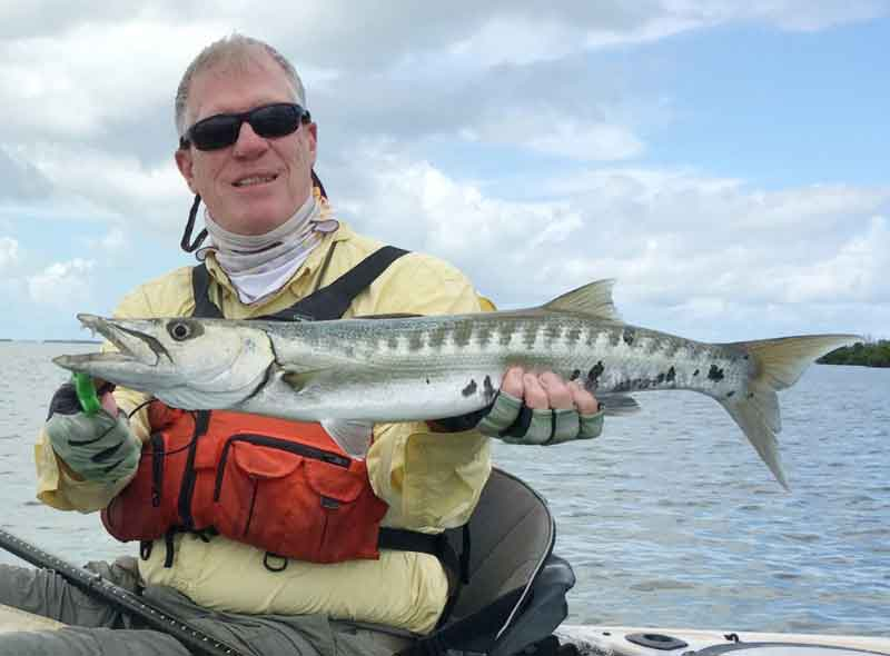 holding up a barracuda caught on a kayak